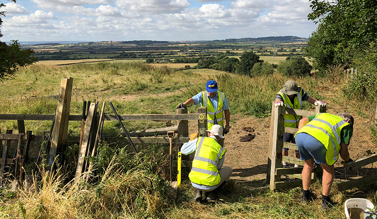 Four men outdoors, wearing high-vis jackets replacing a gate